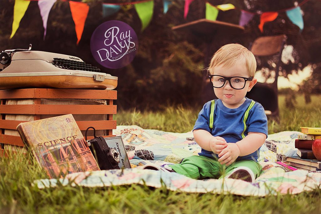 Back To School Mini Session with cute kid in glasses by a typewriter taken by Louisville Photographer Ray Davis