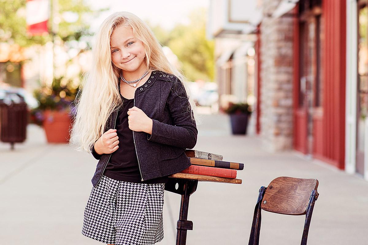 Louisville Tween Girl holding jacket leaning against school desk druing back-to-school photos