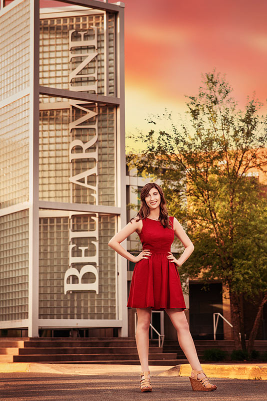 Bellarmine Graduate in Red Dress in front of Bellarmine University Landmark by Louisville Senior Photographer