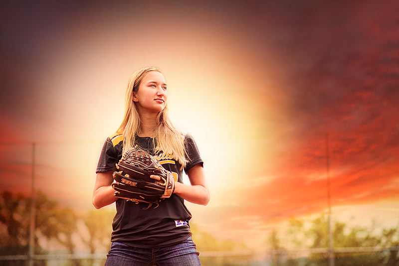 Clarksville High School Softball Senior on field holding glove at Sunset by Louisville Senior Photographer