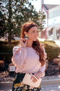 Woman touching flower earrings from Collections Boutique taken by Louisville Social Content Photographer