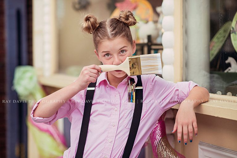 preteen girl using paint brush to make a mustache during louisville tween photo session with Ray Davis Photography