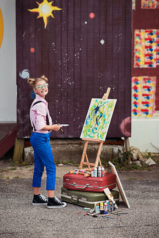 Fun Tween Picture of girl painting on canvas stacked on top of suitcases by Louisville Tween Photographer