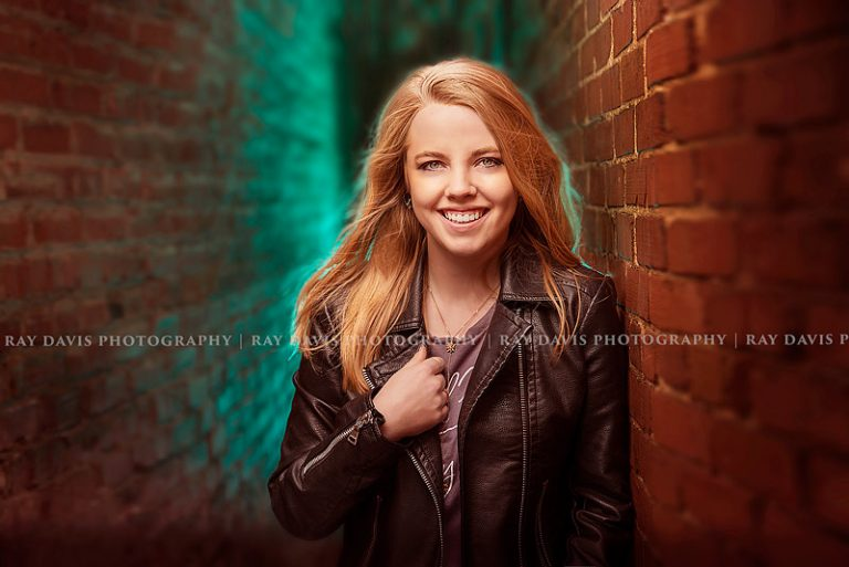 Urban senior girl standing in alleyway with off camera flash blue gels for louisville senior photographer Ray Davis Photography