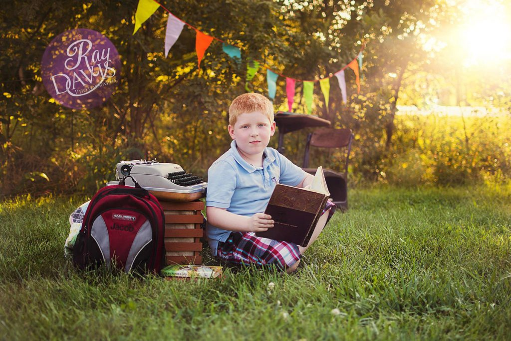 Boy holding science textbook during Back to School Minisessions with Louisville Child Photographer