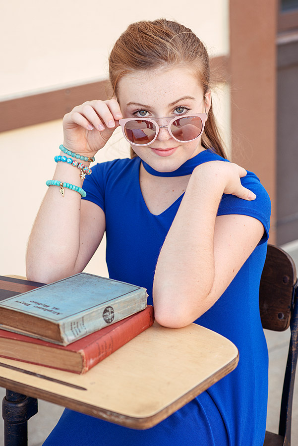 Tween Girl sitting at desk holding glasses from Louisville Tween Photographer Back To School Minisessions