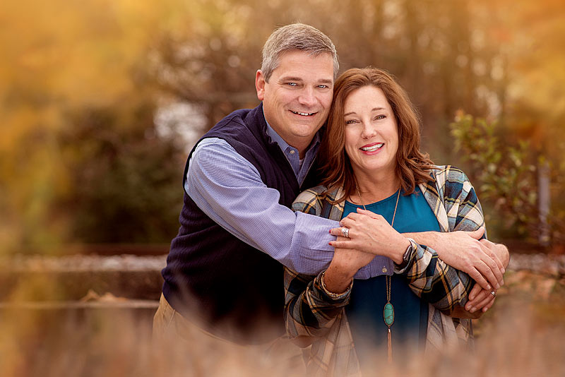 Fall Family Portrait of Husband hugging wife by Louisville Photographer