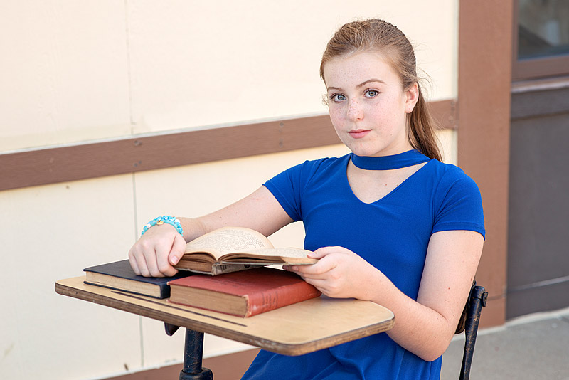 Tween Girl sitting at desk holding book from Louisville Child Photographer Mini Session