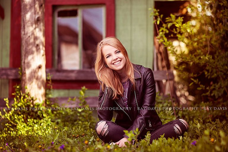 Girl wearing leather jacket sitting in grass for lagrange senior pictures with louisville photographers ray davis photography