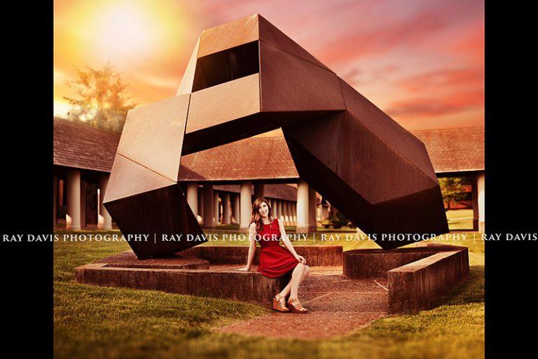 Grad sits under Bellarmine University Campus sculpture in red dress by Ray Davis Photography
