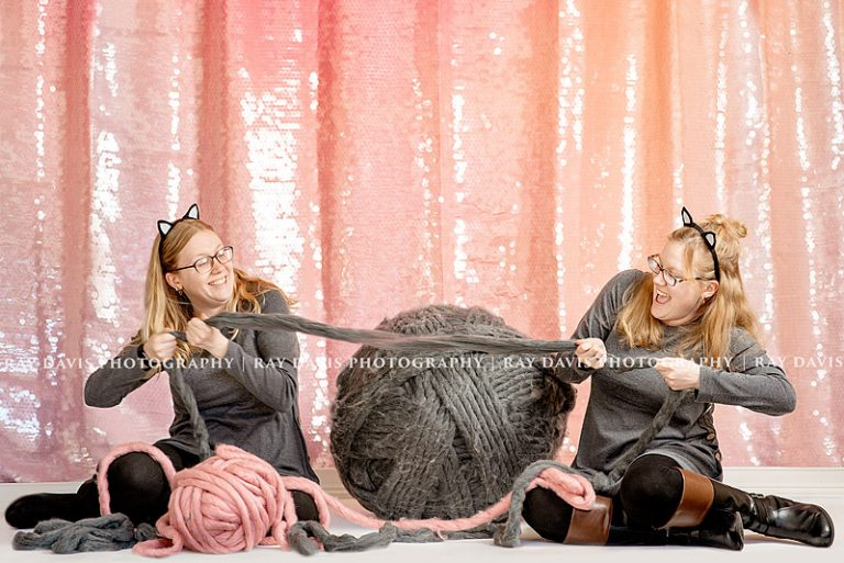 Twins playing tug of war with yarn ball for cat themed 30th Bday session
