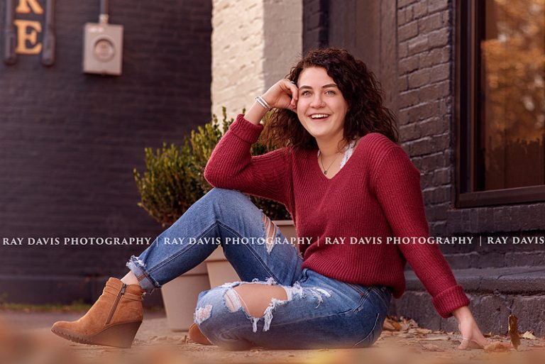 Girl sitting on ground in downtown Louisville for fall senior pictures