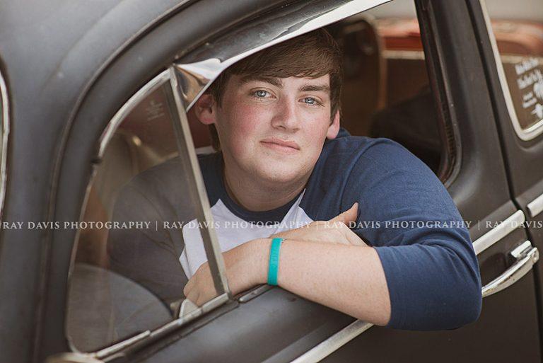 Oldham high school senior guy posed in car window taken by Louisville Photographer