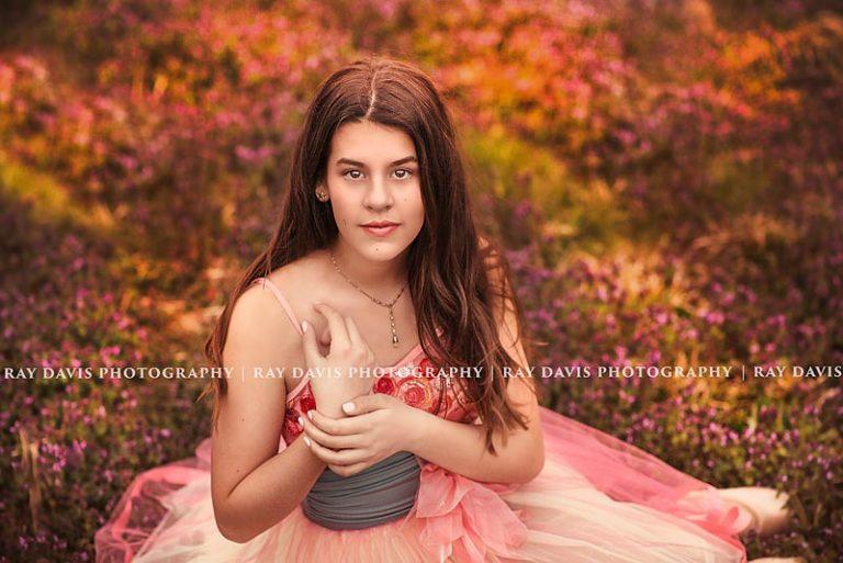 teen ballerina sitting in clover field taken by Ray Davis Photography