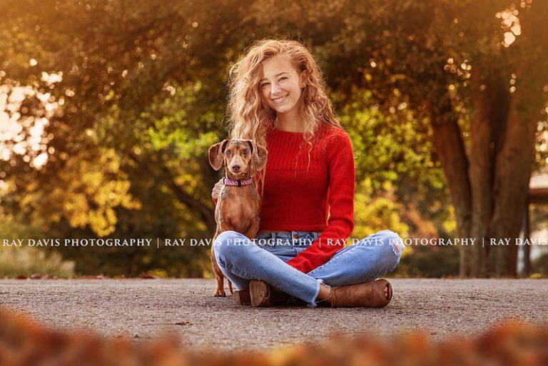 Louisville senior girl sitting on ground with dog taken by Ray Davis Photography